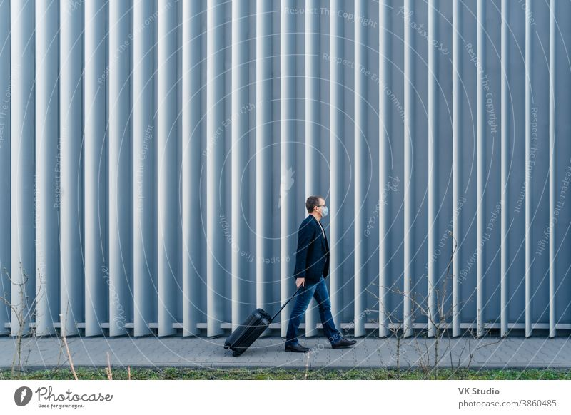 Horizontal panoramic shot of man passenger arrives in own country because of quarantine and pandemic situation in world, walks with suitcase, poses outdoor against metal fence, wears face mask