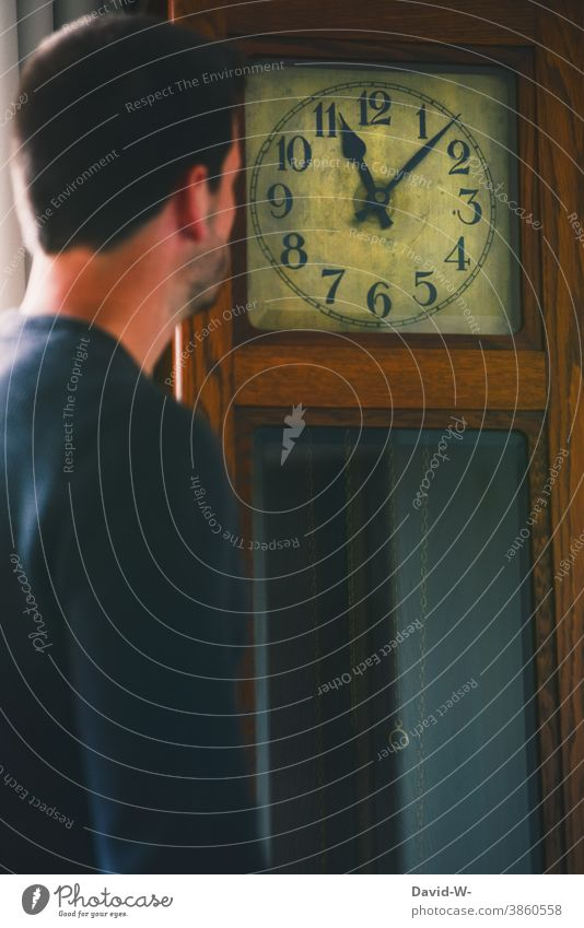 Man looks at a grandfather clock and reads the time Clock Time planning Clock hand Digits and numbers Transience Haste Stress Nostalgia