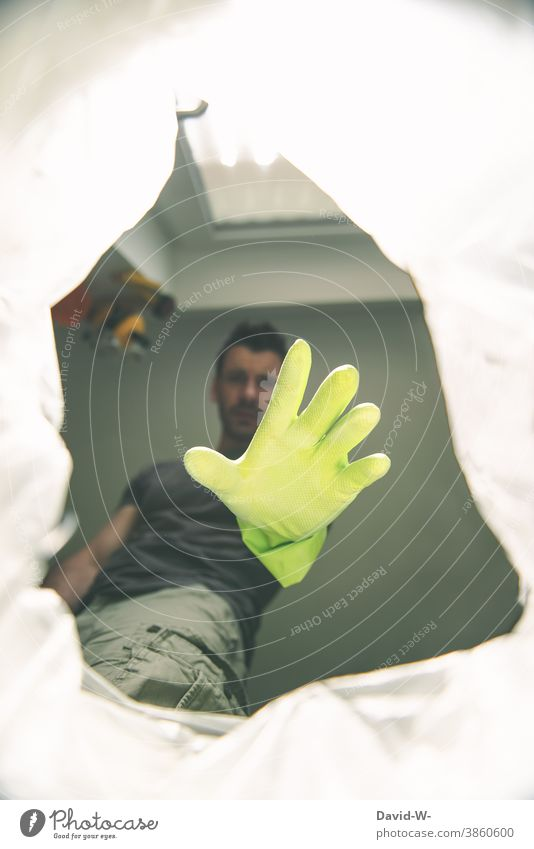 Man reaches with a glove into a trash can / garbage bag Trash Grasp Gloves Disgust waste Hand Trash container Recycling Waste management Dispose of