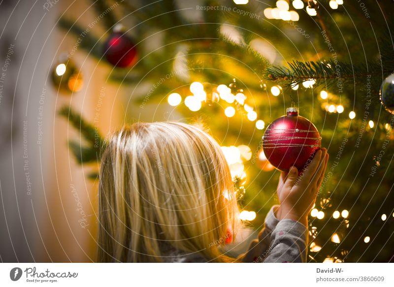 Child holds a Christmas tree ball in his hands in awe Christmas & Advent Glitter Ball reverence awed Cute Anticipation Fairy lights Illuminate