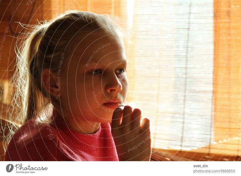 A blonde teenage girl sits by a window in the daylight through a curtain and looks forward thoughtfully, her hand to her chin. Portrait of a pensive blonde girl.
