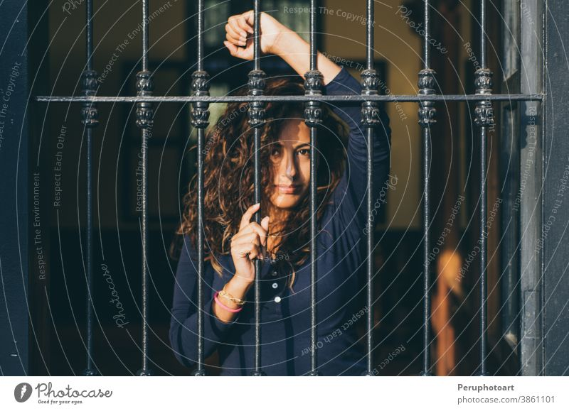 Young girl closed behind bars, network, as in prison face female woman beautiful portrait posing young adult beauty caucasian hair model person pretty sexy