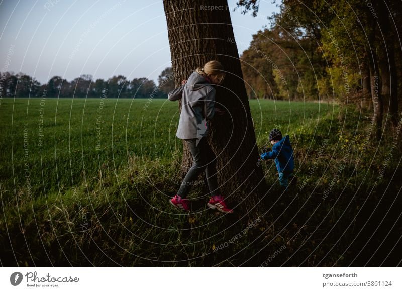 Hide-and-seek during an evening walk children Children's game Evening Dusk Exterior shot Infancy Playing Joy Colour photo Happy Happiness Cute Toddler Girl