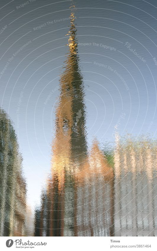 Reflection of a church tower and houses in the water Water Ocean River Lake Town Housefront Warped Distorted surreal Beautiful weather Church spire
