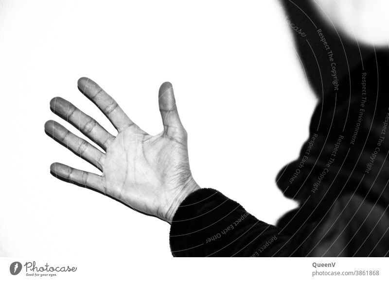 Open hand against a wall with high contrast in black and white fingers palm of the hand violence human gesture Symbols and metaphors rage anger Arm feeling