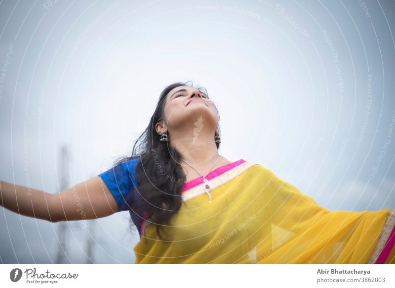 Young and beautiful Indian Bengali brunette woman in Indian traditional yellow sari and blue blouse is standing while spreading her arms on rooftop under blue sky with clouds. Indian lifestyle
