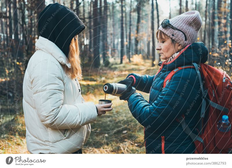 Mother and daughter with backpack having break during autumn trip on autumn cold day active activity adventure backpacker coffee cup destination drink enjoy
