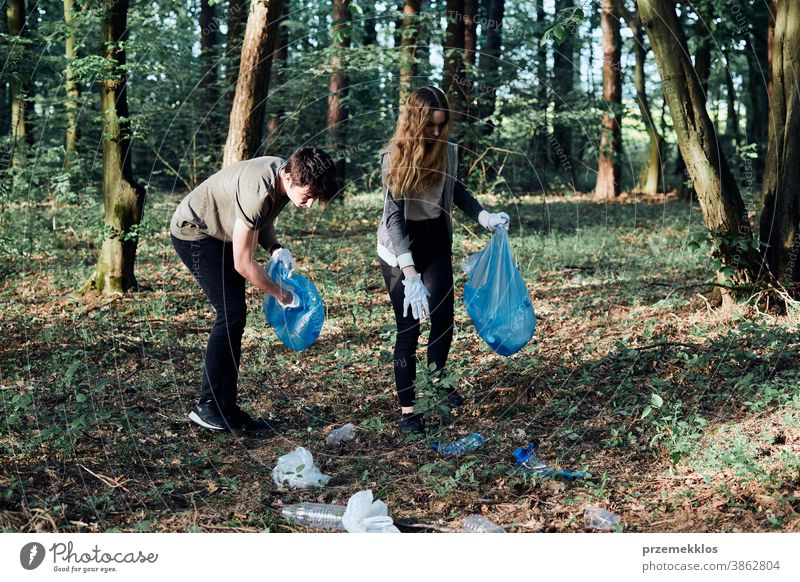 Young man and woman cleaning up a forest. Volunteers picking plastic waste to bags activist bottle care child collect concept ecology environment garbage girl