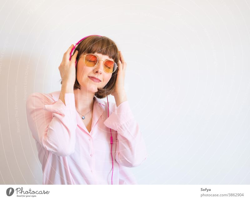 Young happy woman in pink shirt with headphones fashion sunglasses smile music listen engrossed engaged young color lifestyle using technology communication