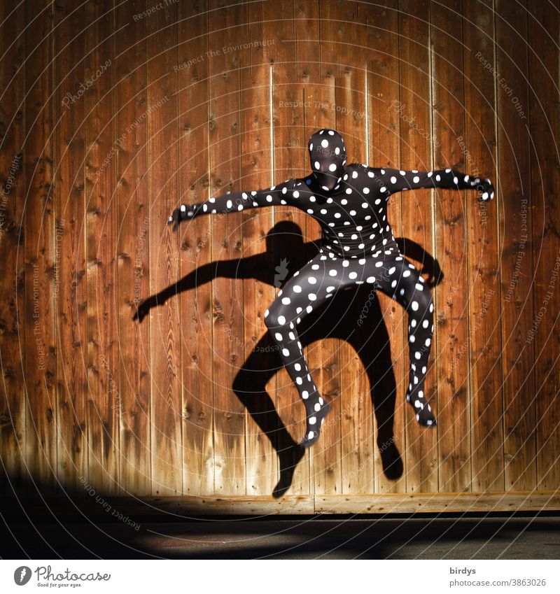 Human figure in dotted morphsuit costume, jumping into the air with shadow cast on a wooden wall Human being Morph Suite full body suit points in a dive