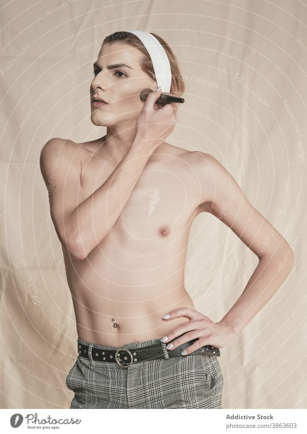 Stylish shirtless guy applying makeup man androgynous appearance rouge style slim hand on waist transgender male young model cheek blusher cosmetic fashion