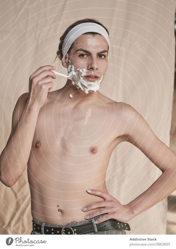 Androgynous young man shaving face shave androgynous transgender hygiene grooming prepare razor shirtless slim male manicure foam skin care hand on waist queer