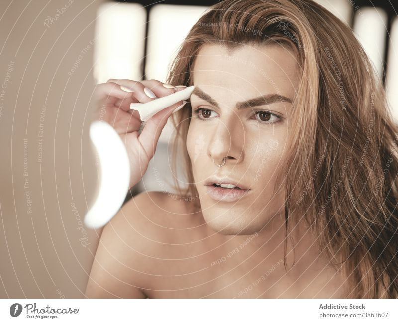 Androgynous male with long hair applying makeup man studio androgynous beauty foundation mirror transgender appearance young model facial pad visage routine