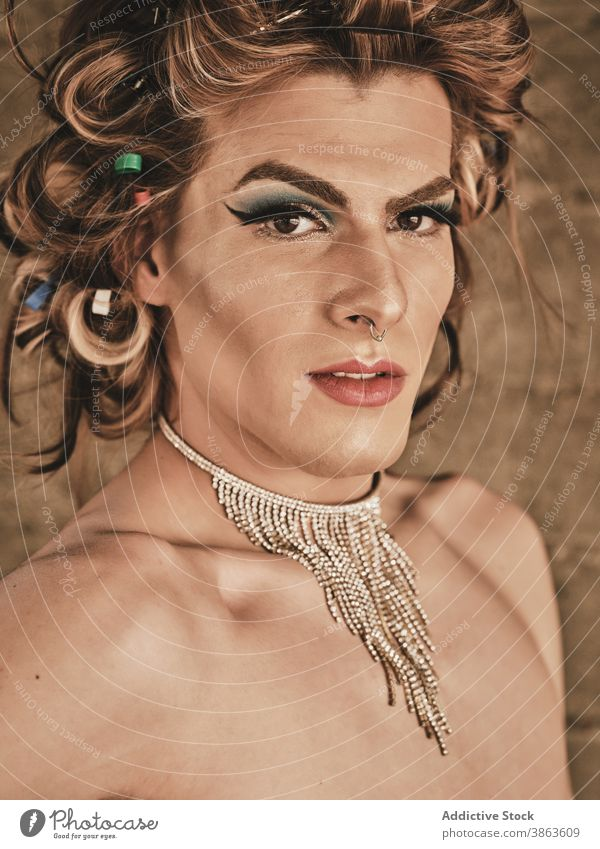 Drag queen with necklace looking at camera man transgender makeup elegant appearance androgynous hairstyle luxury portrait shirtless male young model glamour