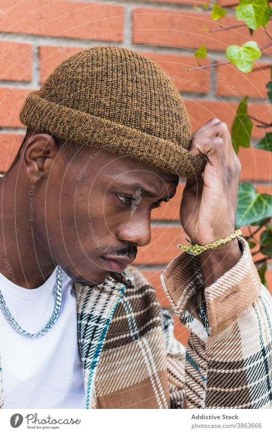 Stylish black man against brick wall street city style urban modern frown casual young male trendy outfit fashion ethnic hipster african american exterior