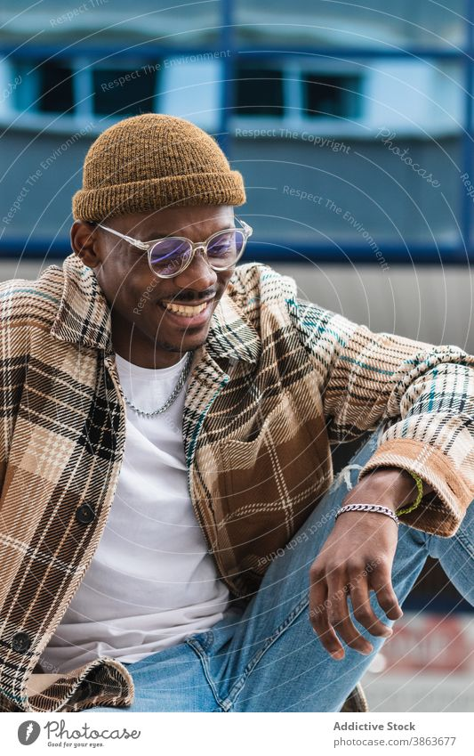 Stylish African American man resting on street city style casual urban modern frown outfit male black ethnic african american young trendy lifestyle town