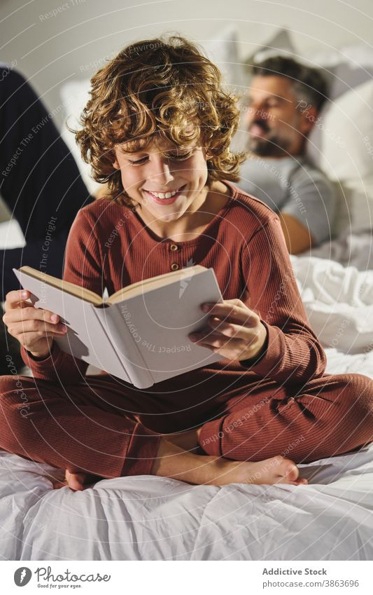 Cute child reading book in room bedroom kid clever entertain father son interesting home story joy literature sit comfort together childhood cozy education