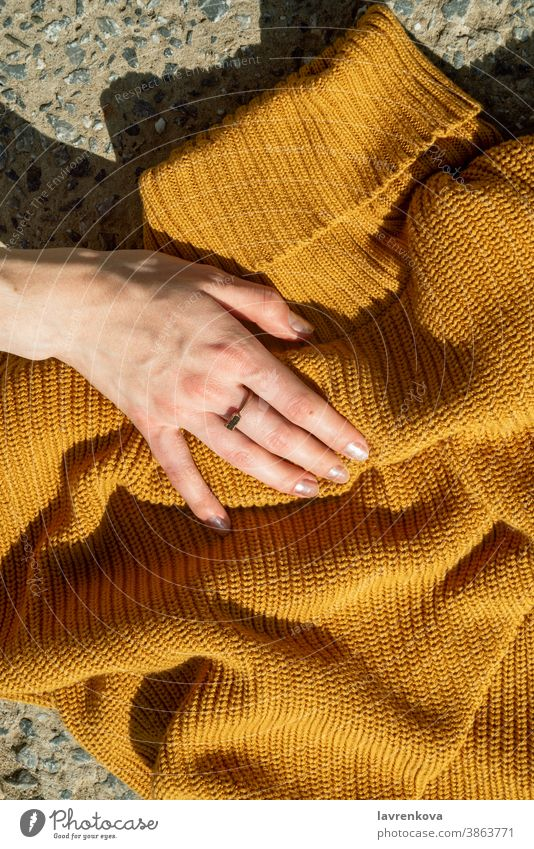 Top view of female hands touching on mustard yellow knit sweater on stone background girl knitted noface faceless stylish urban autumn detail woolen fashion