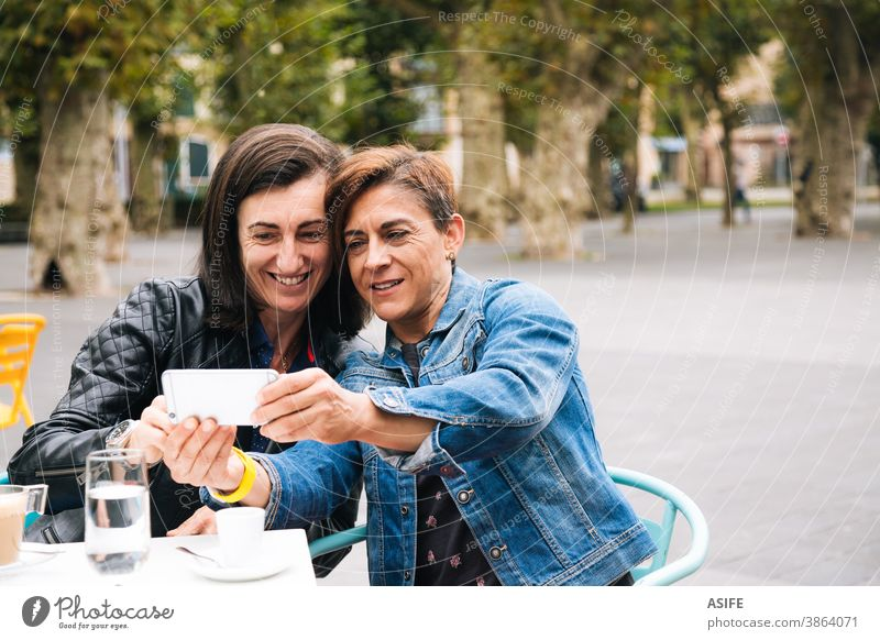 Middle aged lesbian couple taking a selfie LGBTQ gay middle aged 40 50 smart phone self portrait mobile phone smile homosexual women real people candid love
