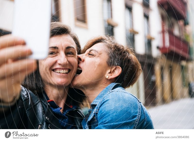 Happy middle aged lesbian couple taking a funny selfie LGBTQ gay 40 50 laughing smartphone self portrait smile embrace hugging holding biting homosexual women