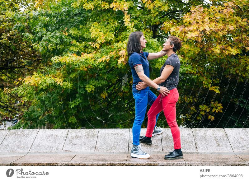 Middle aged lesbian couple enjoying together in the park LGBTQ gay middle aged 40 50 hugging holding embrace smile homosexual women real people candid love