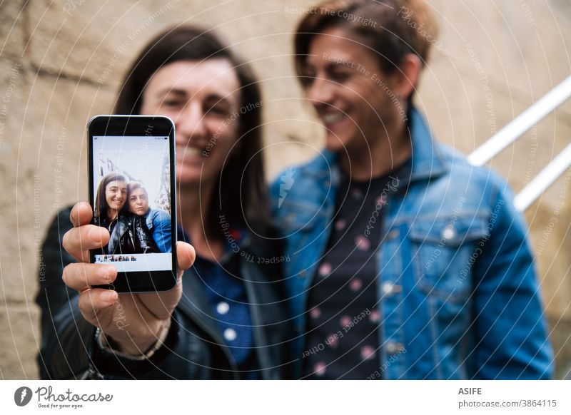 Happy middle aged lesbian couple showing a selfie in the smart phone LGBTQ gay 40 50 laughing smartphone self portrait smile screen embrace hugging holding