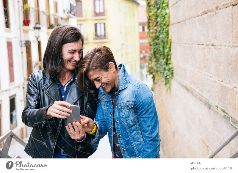 Funny middle aged lesbian couple laughing at something in the mobile phone LGBTQ gay 40 50 selfie smartphone self portrait smile homosexual women real people