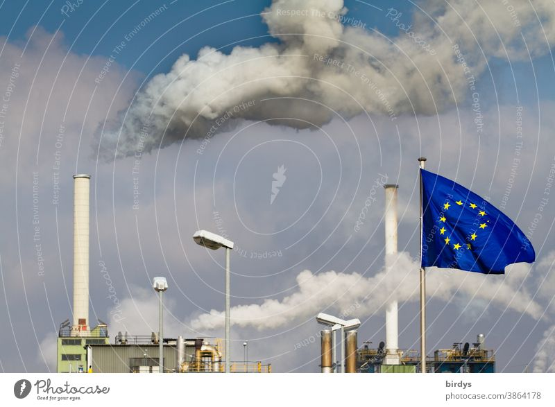 Smoking industrial chimneys . Factory with European flag in front of it .European Union CO2 emission EU Industrial plant Chimney Smoke Air pollution