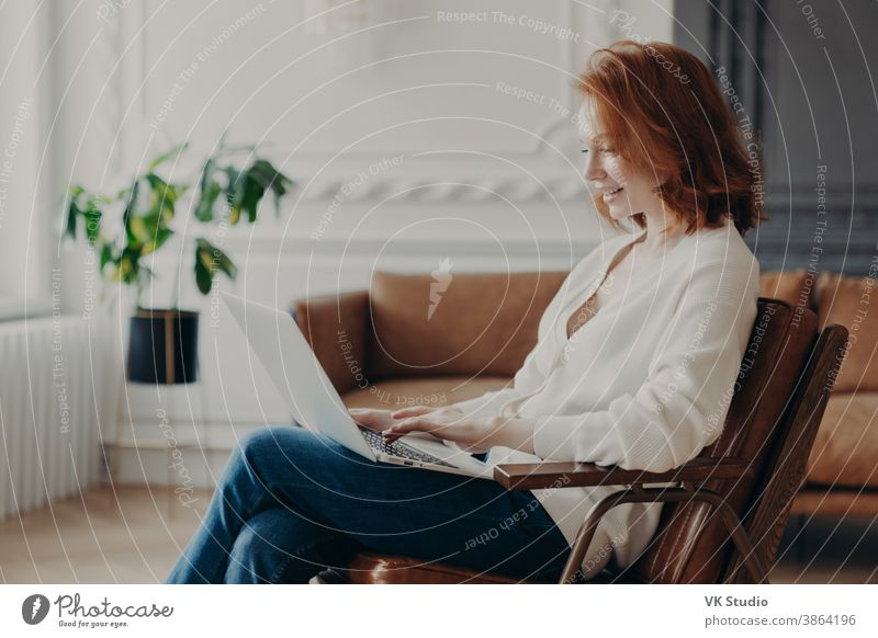 Smiling red haired woman freelancer sits in armchair, keyboards on laptop computer, uploads necessary material for developing site, poses in modern apartment, connected to wireless internet.