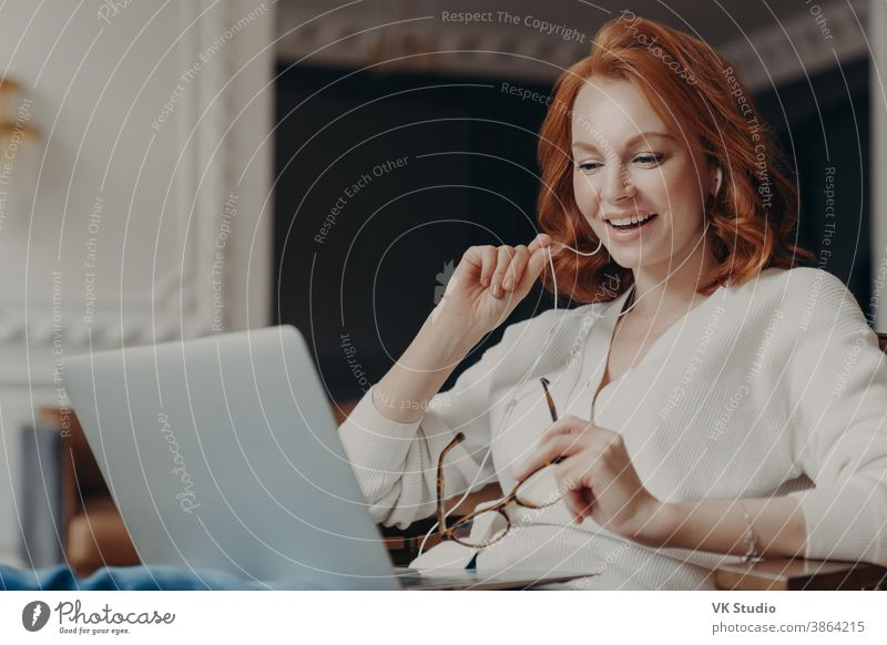 Satisfied happy foxy successful woman has video conference, uses modern laptop computer and earphones, browses data and works on remote project, poses in modern apartment, watches online webinar