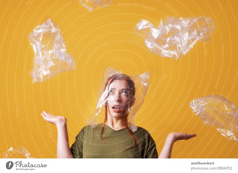 woman overwhelmed by plastic waste and suffocating from plastic bag over her head - ecology and pollution concept suffocate person garbage environment trash