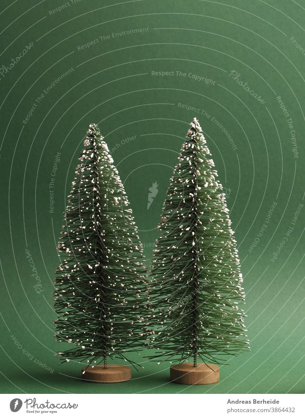 Two fir trees with snow on a green paper background, space for text on top creative traditional snowflake minimal trendy greeting copy space template