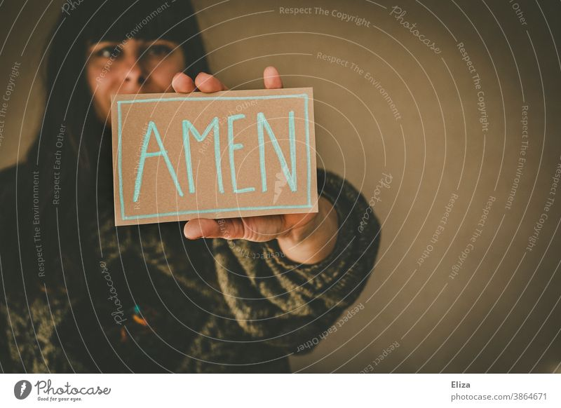 Young woman holding a sign saying Amen amen Church Heart Prayer pray Religion and faith religion Christianity Judaism praying Love Belief believe Holy