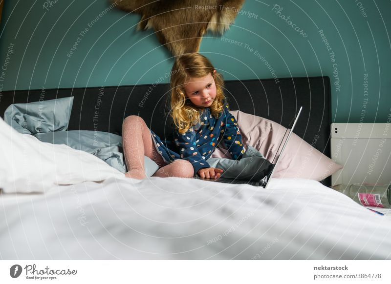Little Caucasian Girl Using Laptop on Bed child girl caucasian laptop bed computer blond 5 years old long shot real life real person lifestyle domestic life
