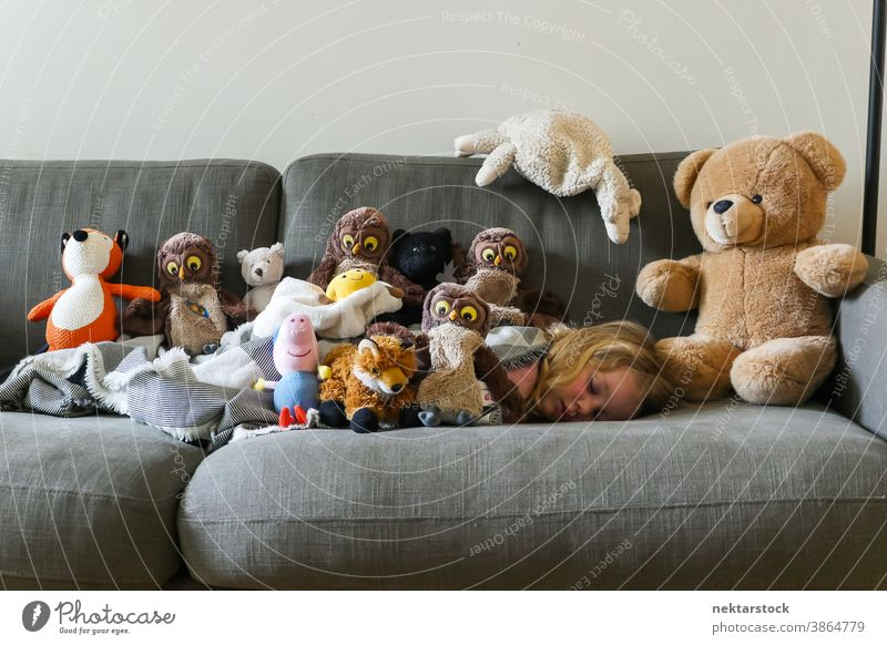 Stuffed Toys Collection on Sofa with Child Sleeping girl sleep toy sofa caucasian stuffed toy teddy bear plush 1 person asleep day nap napping couch collection