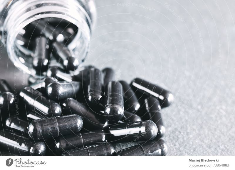 Close up picture of black capsules spill out of container. drug medicine poison addiction danger death treatment medical pharmacy healthy therapy science
