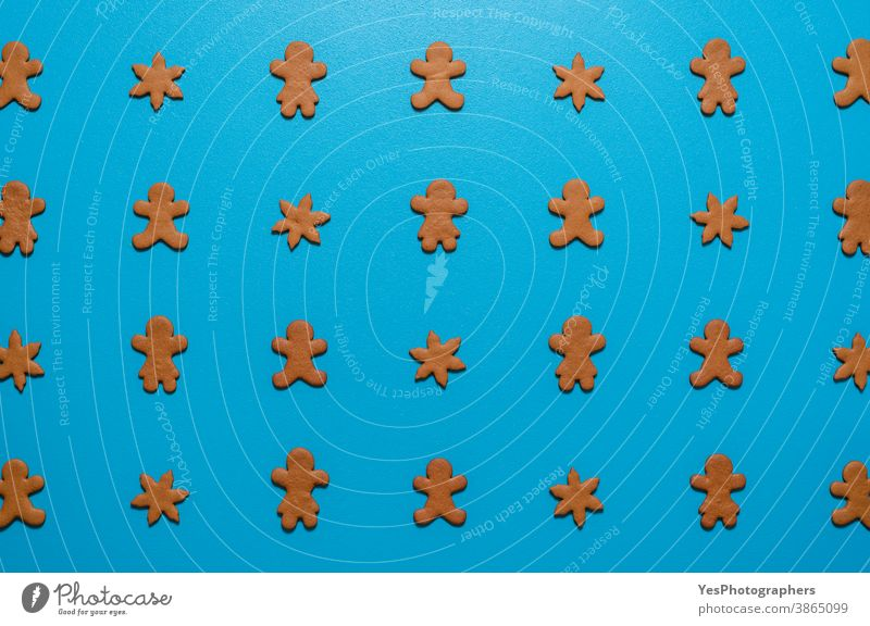Gingerbread cookies flat lay on a blue background. Cookies arranged symmetrically on the table. above view biscuits celebration christmas cut out decoration