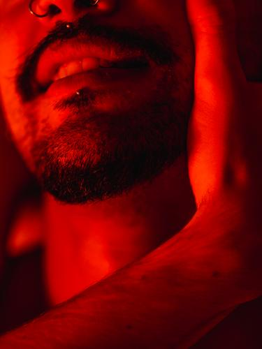 Gay couple during intimate moment in red light homosexual gay love passion romantic bed relationship lgbt ethnic male together affection tender boyfriend beard