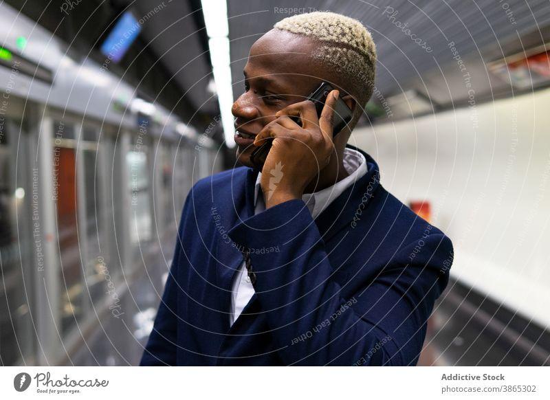 Black businessman talking on smartphone in subway commute work underground entrepreneur speak using male ethnic black african american formal device station