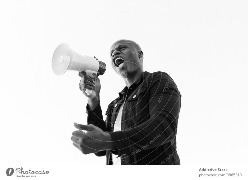 Excited black man with megaphone on white background loudspeaker shout horn announce crazy excited male ethnic african american gesture achieve scream sound