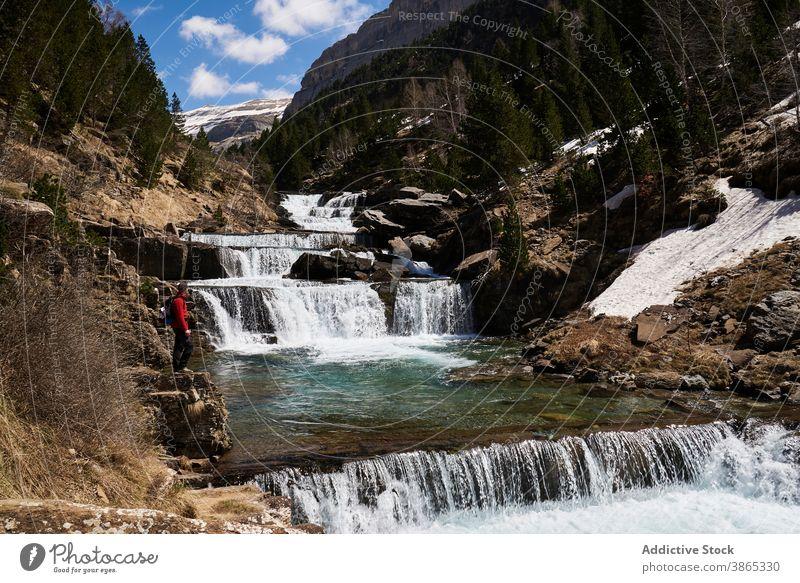 Traveler near cascade waterfall in mountains traveler admire landscape amazing highland terrain scenery pyrenees ordesa valley spain range stream scenic journey