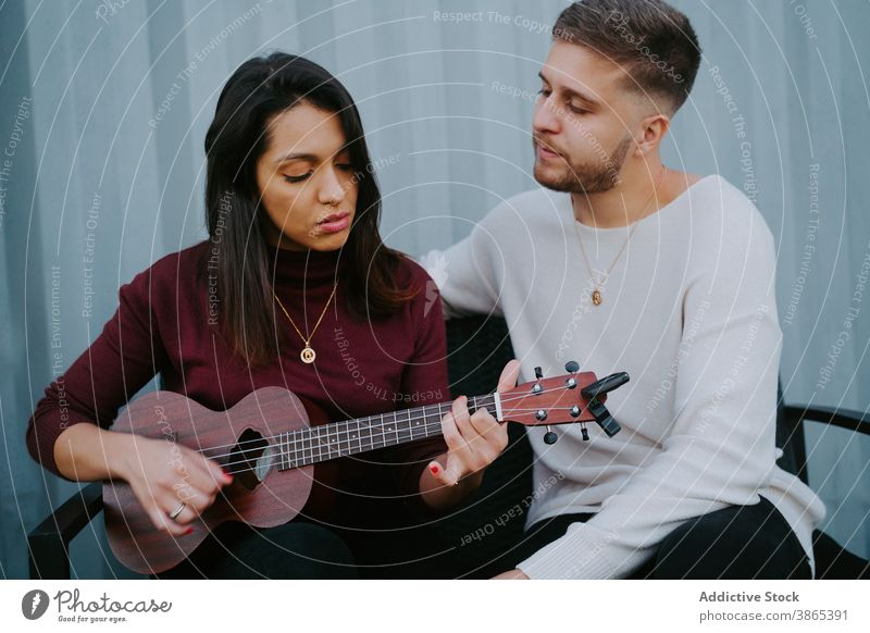 Couple playing ukulele on terrace of compact house couple backyard event relax container music together tranquil relationship song love melody evening dwell