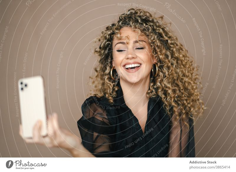 Charming woman taking selfie on smartphone smiling happy self portrait make face lip studio charming female style contemporary trendy gadget device mobile