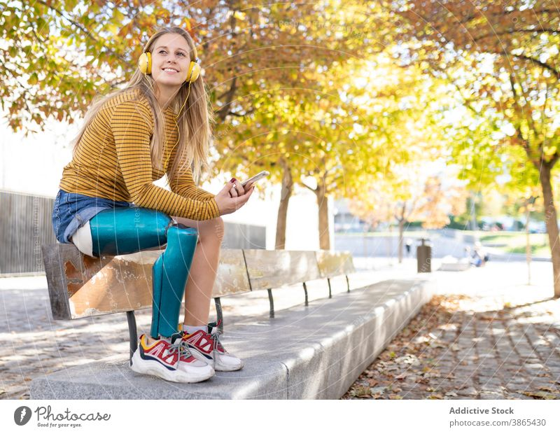 Cheerful woman with leg prosthesis listening to music in headphones bionic street city enjoy female song amputee sunny relax device happy cheerful smartphone