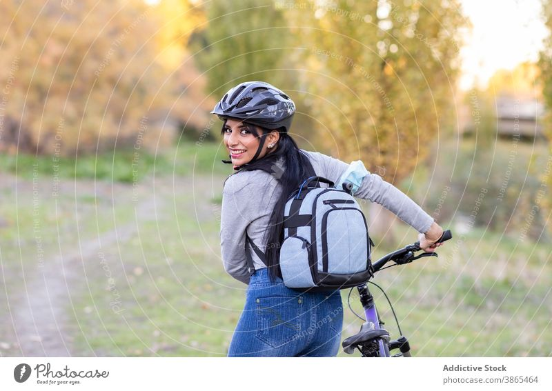 Positive woman with bike in autumn countryside bicycle forest active happy nature ride backpack helmet cheerful female smile trail path activity bicyclist
