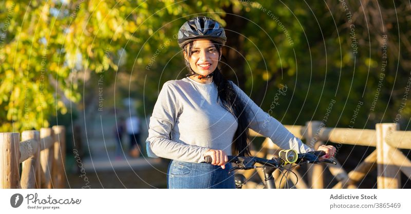 Happy woman riding bike in autumn forest bicycle ride active happy countryside nature cheerful female smile trail path activity bicyclist journey explore young