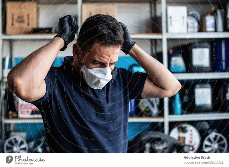 Worker putting white face mask man worker put on glove garage prepare latex uniform busy male staff job employee professional occupation service industry