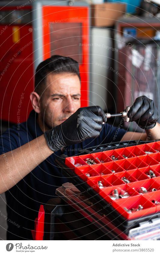Male technician examining tool in garage man mechanic examine box work glove modern professional male adult workplace latex instrument workshop job occupation