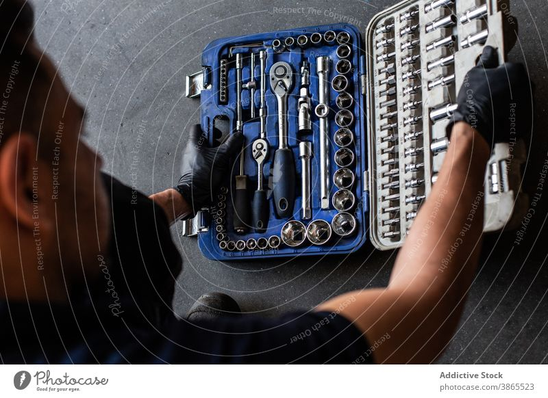 Crop mechanic choosing wrench bit from box man choose garage work professional kit glove male technician latex tool industry fix repair spanner instrument skill
