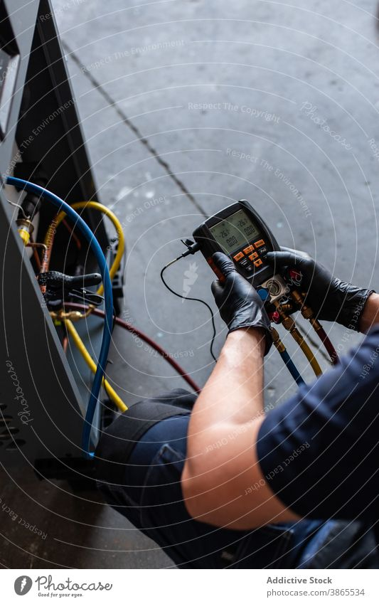 Man checking voltage of broken machine man mechanic tester modern workshop equipment male goggles glove manual busy skill industry job occupation tool workplace